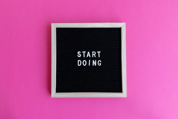 Bovenaanzicht van een schoolbord met een massage op een roze achtergrond