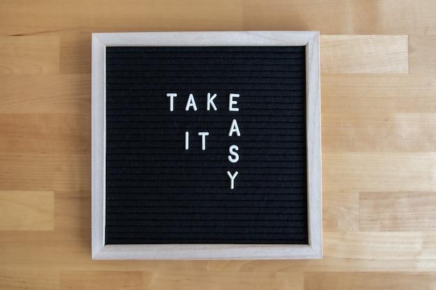Bovenaanzicht van een schoolbord met een rustig citaat erop aan een houten tafel