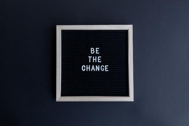 Bovenaanzicht van een schoolbord met een wit frame met een be the change-bericht op een zwarte achtergrond