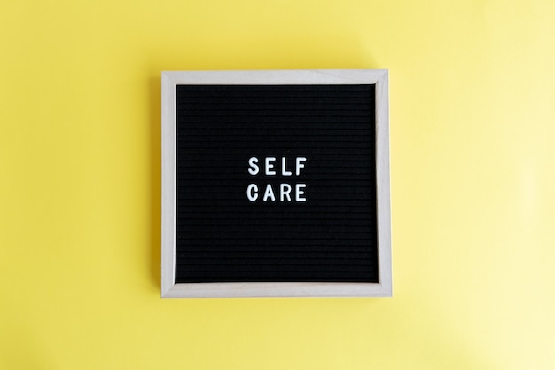 Bovenaanzicht van een schoolbord met een zelfzorgmassage op een gele achtergrond