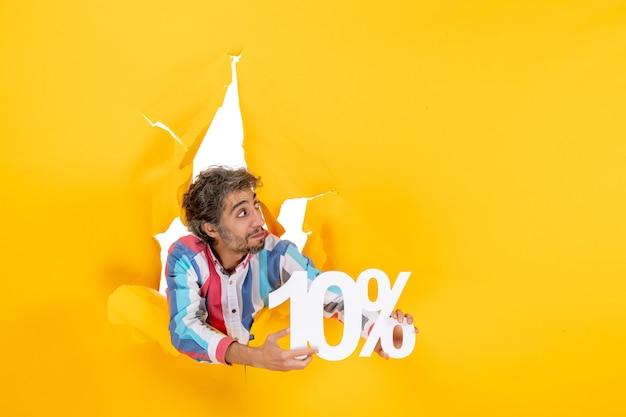 Bovenaanzicht van een serieuze jonge man die tien procent toont in een gescheurd gat in geel papier