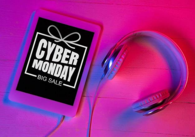 Bovenaanzicht van een set gadgets in paars neonlicht en roze achtergrond tablet en koptelefoon