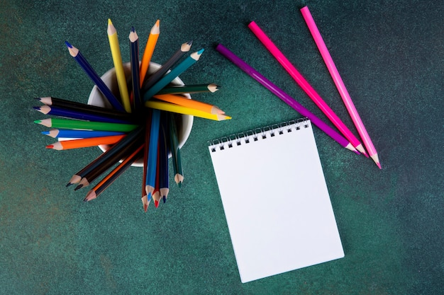 Bovenaanzicht van een set kleurpotloden in een beker en een schetsboek op donkergroen