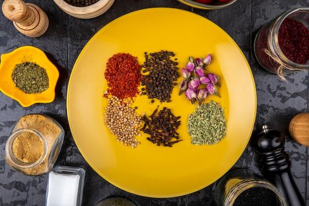 Bovenaanzicht van een set van specerijen en kruiden op een gele plaat en in glazen potten op zwarte achtergrond