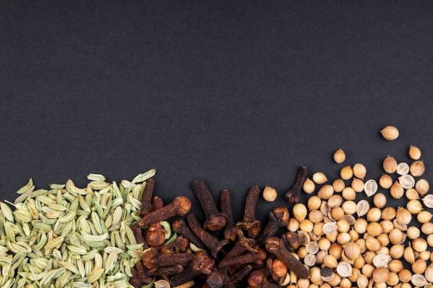 Bovenaanzicht van een set van specerijen en kruiden peperbollen anijszaad en kruidnagel op zwarte achtergrond met kopie ruimte