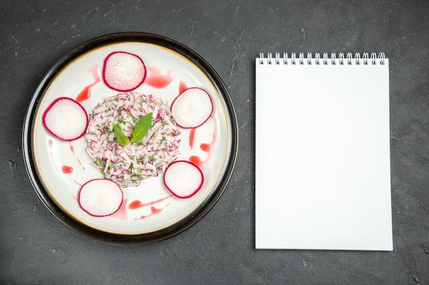 Bovenaanzicht van een smakelijk bord met radijskruiden en saus wit notitieboekje