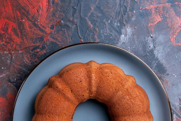 Bovenaanzicht van een smakelijke cake een cake op de blauwe ronde plaat op de donkere tafel