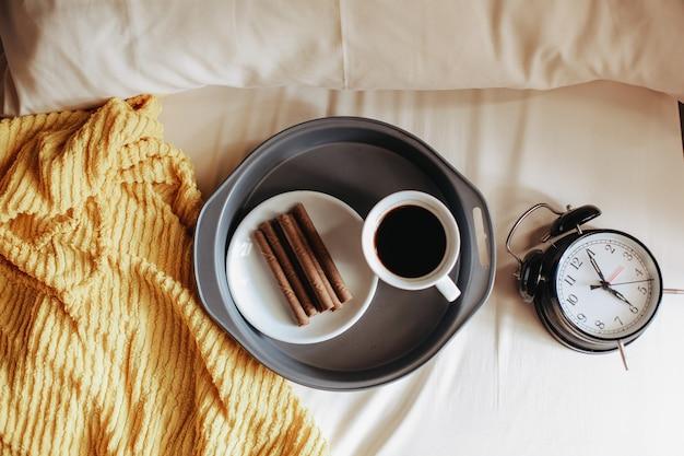 Bovenaanzicht van een snack en een kopje koffie voor het ontbijt met klok 7 uur op het bed