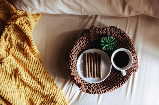 Bovenaanzicht van een snack en een kopje koffie voor het ontbijt op het bed