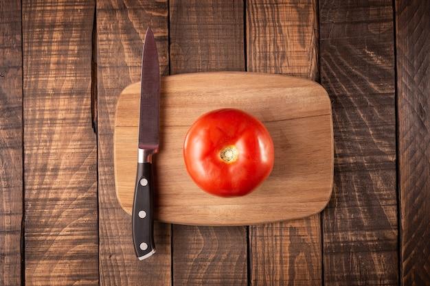 Bovenaanzicht van een snijplank met een tomaat op een houten tafel