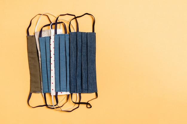 Bovenaanzicht van een stapel van zelfgemaakte textiel herbruikbare maskers op oranje achtergrond. ademhalingsbeschermingsconcept met exemplaarruimte. diy-concept
