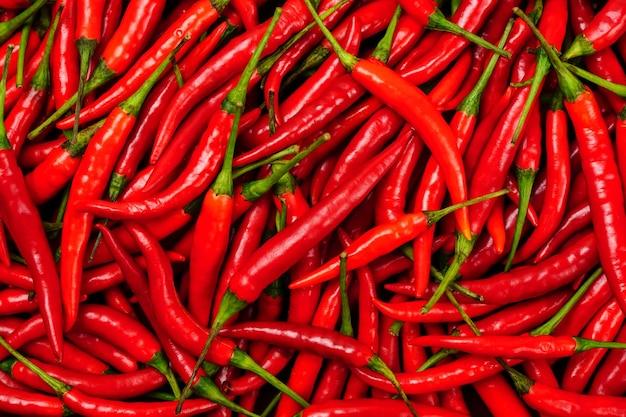 Bovenaanzicht van een stapel verse chili en rijpe rode pepers achtergrondstructuren of sjablonen om te simuleren