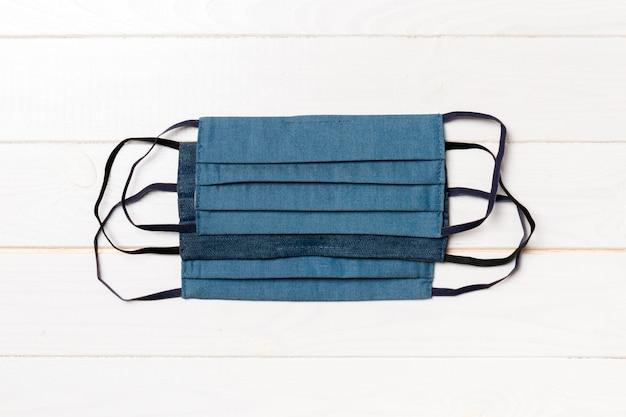 Bovenaanzicht van een stapel zelfgemaakte herbruikbare maskers van textiel op houten achtergrond