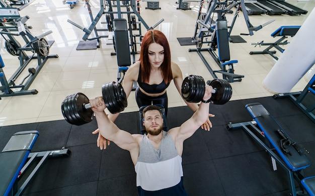 Bovenaanzicht van een sterke man tillen halters en een mooie vrouw helpt hem in de sportschool. actief paar dat met domoren op een moderne sportclub uitoefent.