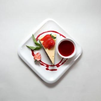 Bovenaanzicht van een stuk cheesecake met een aardbei op een bord geïsoleerd op een witte achtergrond
