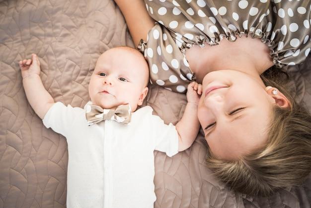 Bovenaanzicht van een tienermeisje knuffelen haar charmante pasgeboren broer liggend op bed met een fopspeen.