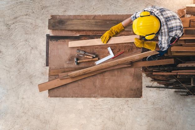 Bovenaanzicht van een timmerman die werkt met houtbewerkingsmachines in een timmermanswerkplaats de timmerman werkt aan de bouw van het huis in het bouwgebied.