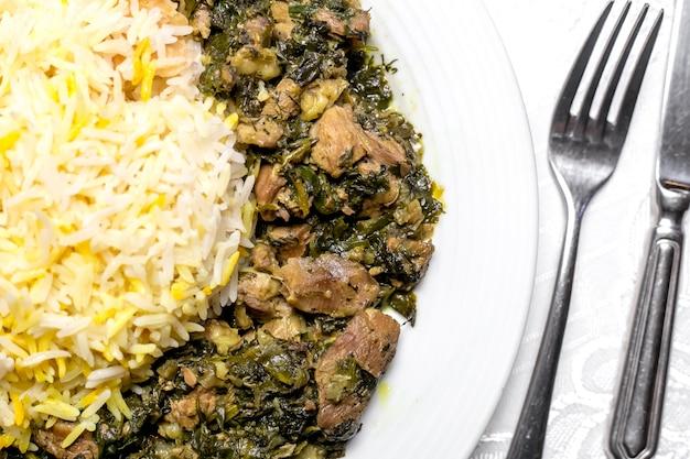 Bovenaanzicht van een traditioneel azerbeidzjaans gerecht syabzi pilaf gebakken vlees met groenten en gekookte rijst
