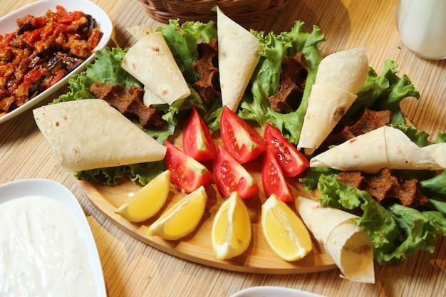 Bovenaanzicht van een traditionele turkse schotel rauwe kotelet kyufta met pitabroodjes tomaten en citroen met sla op een standaard
