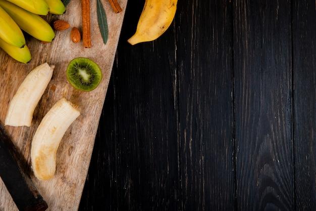 Bovenaanzicht van een tros bananen met amandel, kaneelstokjes en oude keukenmes op een houten snijplank op zwart met kopie ruimte