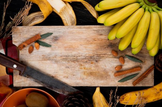 Bovenaanzicht van een tros bananen met amandel, kaneelstokjes en oude keukenmes op een houten snijplank op zwart