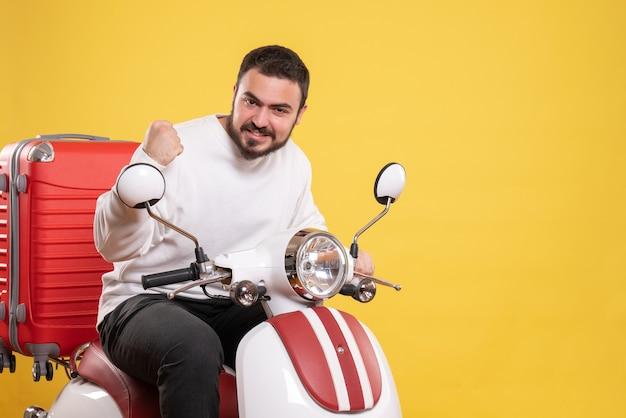 Bovenaanzicht van een trotse jonge kerel die op een motorfiets zit met een koffer erop en geniet van zijn succes op een geïsoleerde gele achtergrond