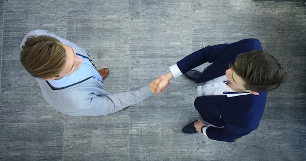 Bovenaanzicht van een twee zakenman handen schudden. welkom in het bedrijfsleven.