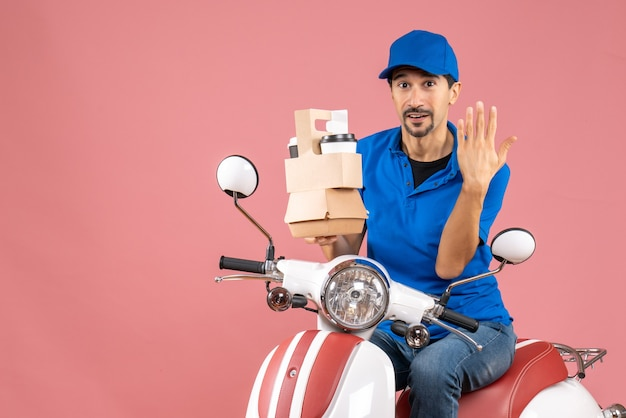 Bovenaanzicht van een vastberaden koeriersman met een hoed die op een scooter zit en bestellingen vasthoudt met vijf op een pastelkleurige perzikachtergrond