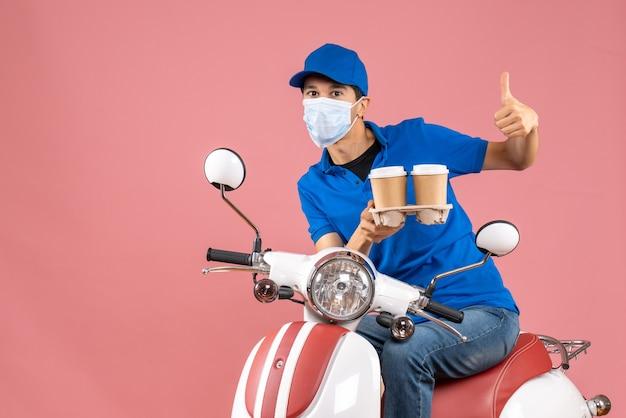 Bovenaanzicht van een vastberaden koeriersman met een masker met een hoed die op een scooter zit en orders toont die een goed gebaar maken op een pastelkleurige perzikachtergrond