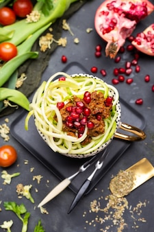 Bovenaanzicht van een veganistische maaltijd met spiraalvormige courgette, tomatensaus en granaatappels in de beker