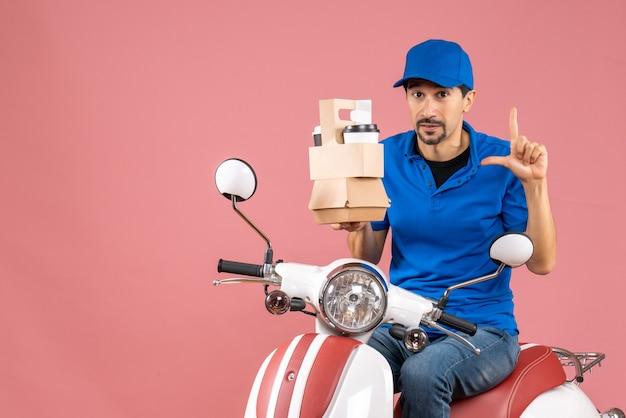 Bovenaanzicht van een verbaasde koeriersman met een hoed die op een scooter zit en bestellingen op pastel perzik toont