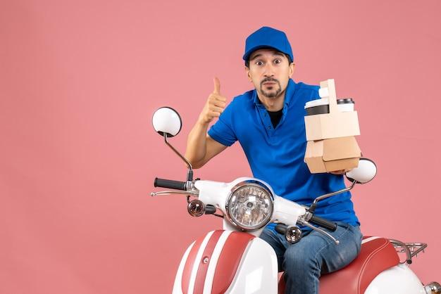 Bovenaanzicht van een verbaasde koeriersman met een hoed die op een scooter zit en orders toont die een goed gebaar maken op pastel perzik