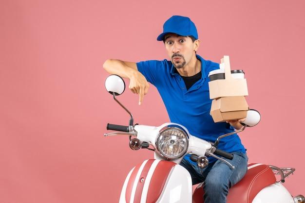 Bovenaanzicht van een verbaasde koeriersman met een hoed die op een scooter zit en orders toont die naar beneden wijzen op pastel perzik