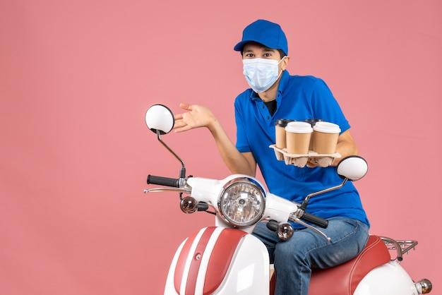 Bovenaanzicht van een verbaasde koeriersman met een masker met een hoed die op een scooter zit en bestellingen op pastel perzik toont