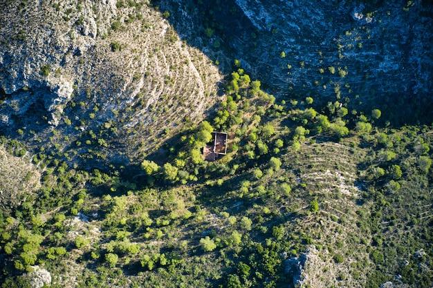 Bovenaanzicht van een verlaten huis omgeven door groen