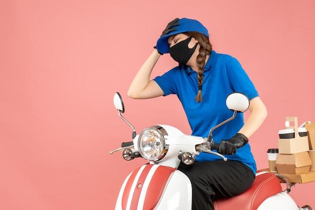 Bovenaanzicht van een vermoeid koeriersmeisje met een medisch masker en handschoenen die op een scooter zitten en bestellingen afleveren op pastel perzik