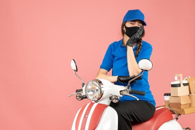 Bovenaanzicht van een vermoeide koeriersvrouw met een medisch masker en handschoenen die op een scooter zit en bestellingen aflevert op pastel perzik