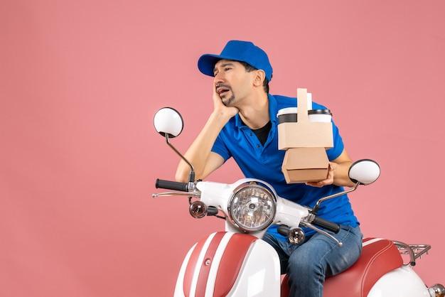 Bovenaanzicht van een verontruste koeriersman met een hoed die op een scooter zit en bestellingen op pastel perzik toont