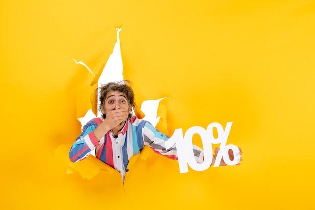 Bovenaanzicht van een verraste bebaarde man met tien procent in een gescheurd gat in geel papier