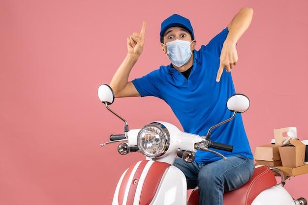 Bovenaanzicht van een verraste bezorger met een medisch masker met een hoed op een scooter die op en neer wijst op pastel perzik