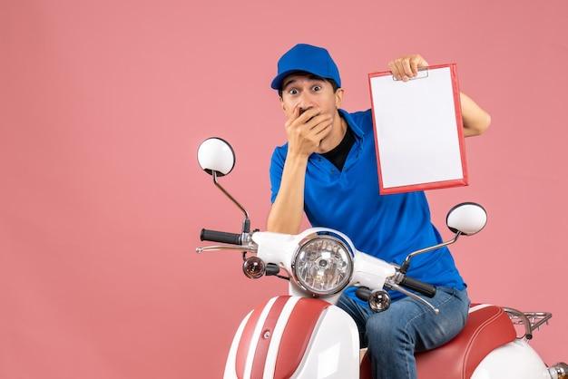 Bovenaanzicht van een verraste, geschokte koeriersman met een hoed die op een scooter zit en een document vasthoudt op pastel perzik