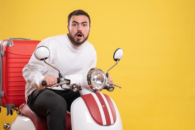 Bovenaanzicht van een verraste jonge kerel die op een motorfiets zit met een koffer erop op geel