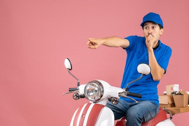 Bovenaanzicht van een verraste koeriersman met een hoed die op een scooter zit en bestellingen aflevert die naar voren wijzen op pastel perzik