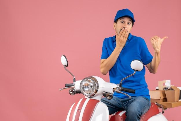 Bovenaanzicht van een verraste koeriersman met een hoed die op een scooter zit en bestellingen aflevert die terug wijzen op pastel perzik