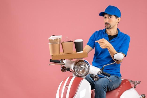 Bovenaanzicht van een verraste koeriersman met een hoed die op een scooter zit en naar voren wijst op pastel perzik