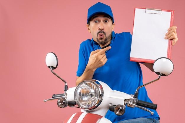 Bovenaanzicht van een verraste mannelijke bezorger met een hoed die op een scooter zit met document