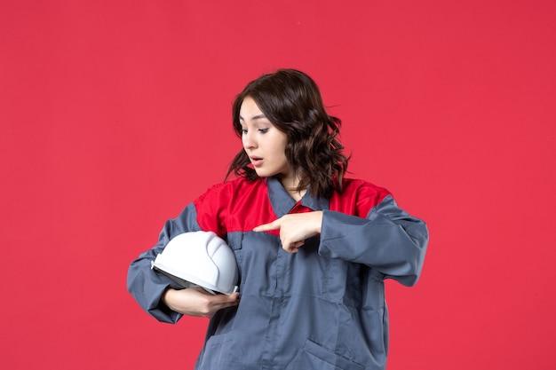 Bovenaanzicht van een verraste vrouwelijke architect die een helm vasthoudt en deze op een geïsoleerde rode achtergrond richt