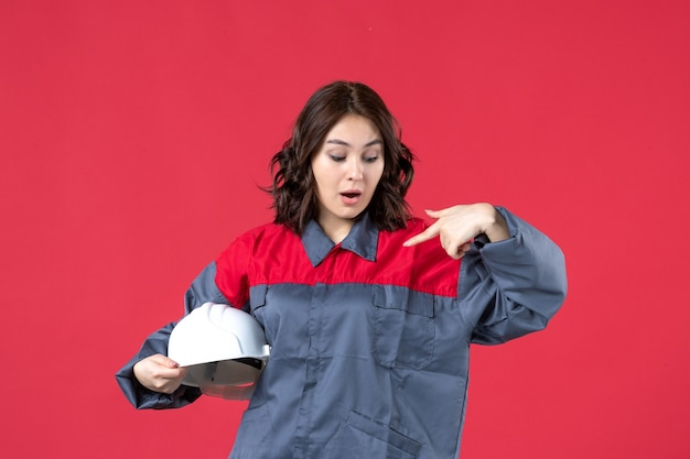 Bovenaanzicht van een verraste vrouwelijke architect die een helm vasthoudt en zichzelf wijst op een geïsoleerde rode achtergrond