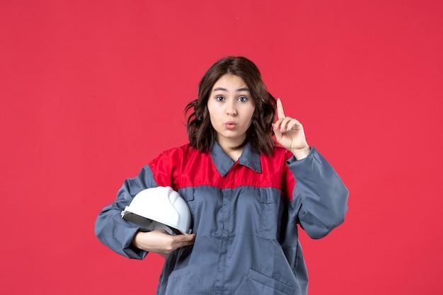 Bovenaanzicht van een verraste vrouwelijke bouwer in uniform en met een helm die omhoog wijst op een geïsoleerde rode achtergrond