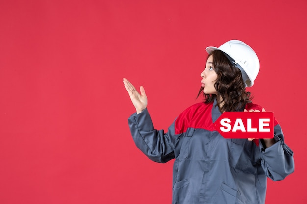 Bovenaanzicht van een verraste vrouwelijke bouwer in uniform met een helm en een verkooppictogram dat aan de rechterkant op geïsoleerde rode achtergrond omhoog wijst